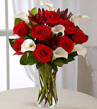 Classic red roses blend with the elegance of white calla lilies